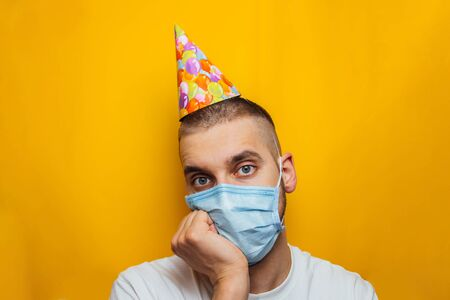 Young Caucasian guy in a medical mask celebrates his birthday. The patient is sitting and sad looking side. The concept of loneliness in quarantine during the pandemic of the coronavirus COVID-19