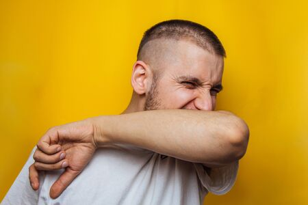 Caucasian man coughs in his elbow and holds hand on chest, experiencing pain. Correct sneezing. Concept of spread of the virus. Isolated on a yellow background.