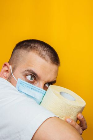A young man in a medical mask holds rolls of toilet paper, shows a dangerous gesture on a yellow background. Stock concept, shortage, panic and quarantine