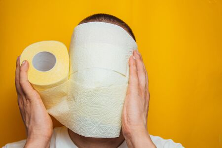 A man in a blue shirt wrapped his face in toilet paper, trying to protect himself from the coronavirus. In the studio on a yellow background. Protecting health from viruses