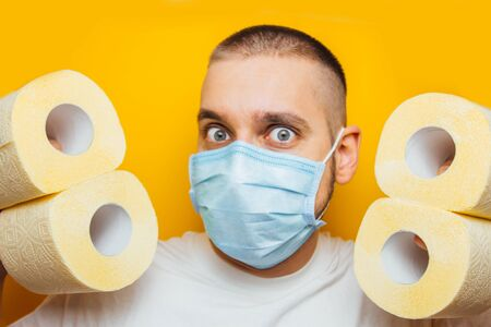 A handsome guy in a protective mask hides behind a wall of toilet paper to prevent coronavirus infection. Yellow background. Flash concept COVID-19. Home insulation