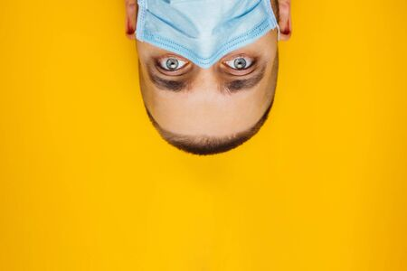 Closeup portrait of an attractive young man rolled his eyes in a protective mask on his face. Fear of getting sick, coronavirus concept. Without pupils.Looks from top to bottom
