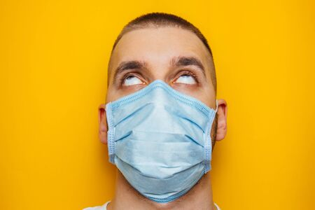 Closeup portrait of an attractive young man rolled his eyes in a protective mask on his face. Fear of getting sick, coronavirus concept. Without pupils