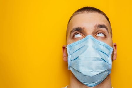 Closeup portrait of an attractive young man rolled his eyes in a protective mask on his face. Fear of getting sick, coronavirus concept. Without pupils. Advertising, place for text