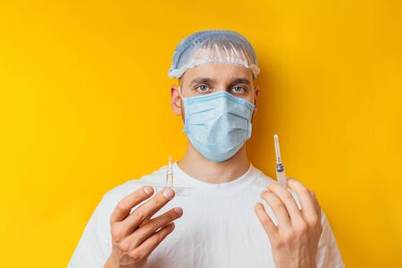Portrait of a young guy in a respirator on a yellow background. Holding an ampoule with a coronavirus vaccine. Cold medicine. The concept of coronavirus