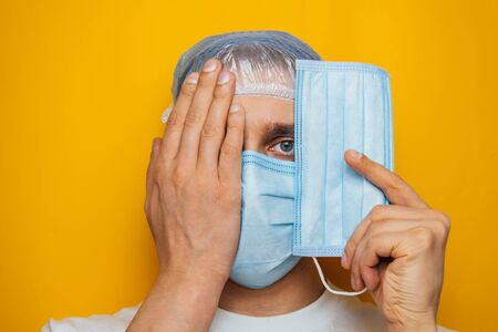 The guy puts on a respiratory mask over his eyes. Attractive man puts on a mask and looks at the camera. Colds, flu, virus, tonsillitis, acute respiratory infections, quarantine, epidemic concept