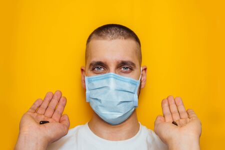 The guy in the mask holds a pill from the coronavirus in his hands. Vitamins to strengthen the immune system. Sit at home. Colds, flu, virus, quarantine, epidemic concept. Difficult choice