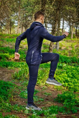 Handsome, young guy in a tracksuit plays sports in the park on the nature. Healthy lifestyle