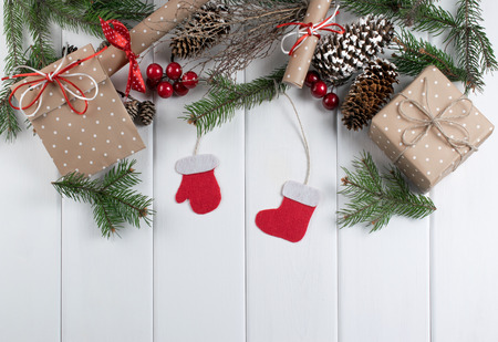 Christmas background with Santa Claus boot and mitten, spruce, gift box and scrolls on wooden boards. New Year holidays concept. Top view. Stock Photo