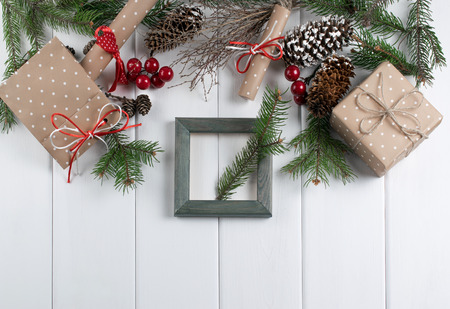 Christmas background with photo frame, spruce, gift box and scroll on wooden boards. New Year holidays concept. Top view. Stock Photo