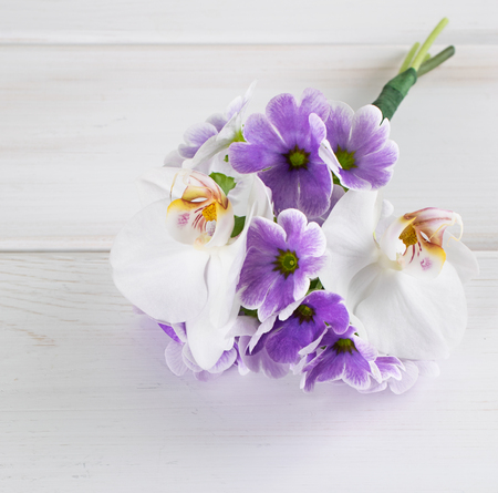 Bouquet of violet primroses and  orchid on background of wooden planks in Shabby Chic style