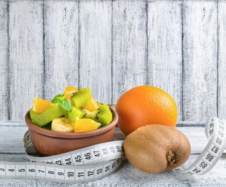 morsel: Fruit salad with kiwi, banana and orange for slimming, centimeter on the wooden board Stock Photo