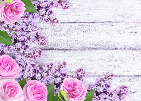 fiori lilla con rose selvatiche su tavole di legno squallido. Roses sfondo.