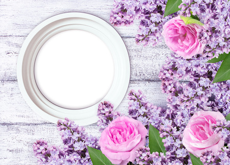 Lilac flowers with roses and round photo frame on background of shabby wooden planks Stock Photo