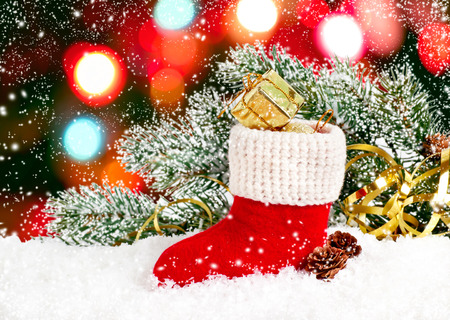 Santas boot with gift box and cones on snow on boke background
