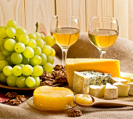 stilton: White wine with blue cheese, camembert and swiss cheese, honey, walnuts and grapes on sackcloth on a background of a wooden wall and autumn leaves Stock Photo
