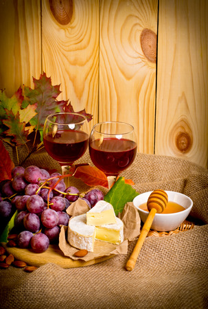 tabla de quesos: Red wine with cheese, honey, almonds and grapes on sackcloth on a background of a wooden wall and autumn leaves