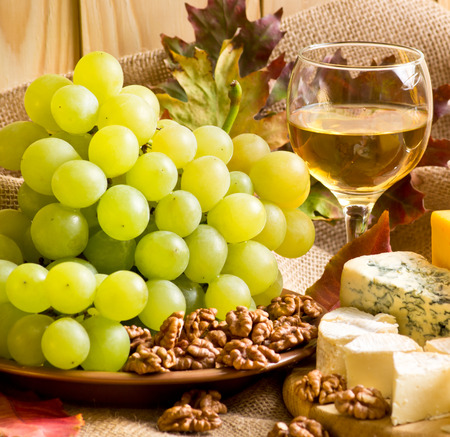 White wine with blue cheese, camembert cheese, walnuts and grapes on sackcloth on a background of a wooden wall and autumn leaves Stock Photo