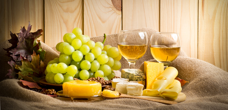 Vino bianco con formaggio blu, camembert e formaggio svizzero, noci, miele e uva su tela di sacco su uno sfondo di una parete in legno e foglie d'autunno Archivio Fotografico - 66826070