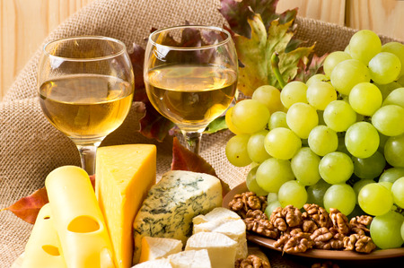stilton: White wine with blue cheese, camembert and swiss cheese, walnuts and grapes on sackcloth on a background of a wooden wall and autumn leaves