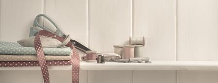 coser: diseño de interiores para la costurera. Conjunto de carretes de hilo, centímetro, tela, dedal y tijeras, Abreojales, agujas y alfileres de costura y la costura en el estante de madera
