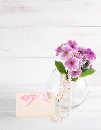 Bouquet of primroses in round vase with paper greeting card and womens pearl necklace Stock Photo