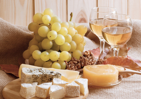 stilton: Various types of cheese served with grapes, walnuts, honey and white wine on sackcloth and wooden planks background