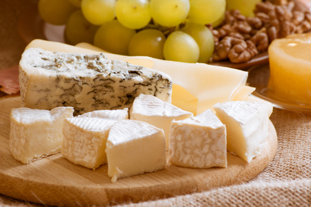 stilton: Various types of cheese served with grapes, walnuts and honey on sackcloth Stock Photo