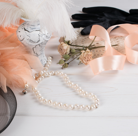 table decoration: Womens retro accessories including velvet gloves and pearl necklace on wooden  table