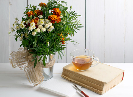 Old book and wooden nib pen with sheet paper and tagetes bouquet on wooden board in shabby chic style Stock Photo