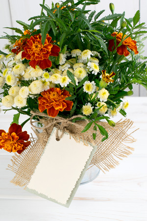 Tagetes flower bouquet with decorative greeting card on white wooden boards in shabby chic style
