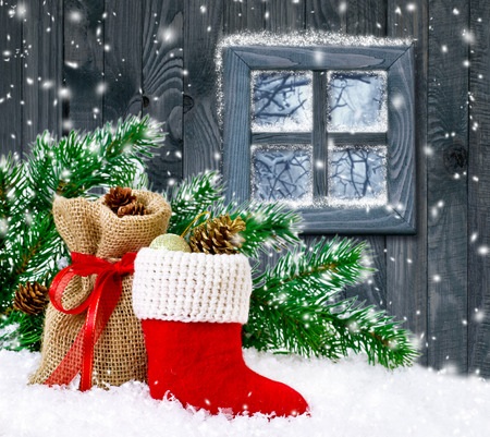botas de navidad: Santa boot and bag with gifts and cones on wooden wall background and forest outside the window
