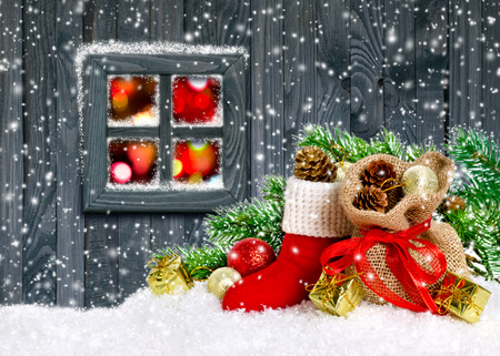 Santas boot and bag with gifts and cones on wooden wall background and glowing lights outside the window Stock Photo