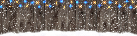 Christmas banner with glowing lights and sparkle garland on wooden planks background