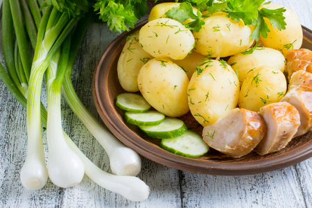 Young boiled potatoes with dill in the bowl, sausage and cucumber on the plate, parsley and onions on the wooden board