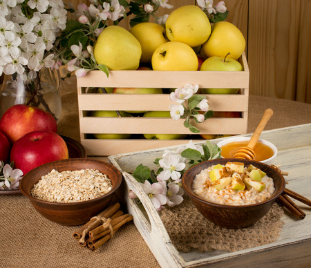 Oatmeal with apple and cinnamon in the bowl, honey and cinnamon sticks on the wooden tray, apples in a crate
