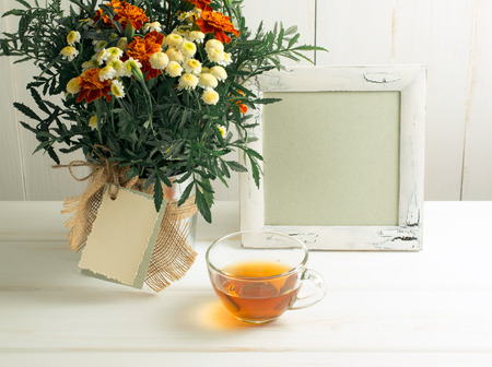 Tagetes flower bouquet with decorative greeting card, photo frame and cup of tea  on white wooden boards in shabby chic style