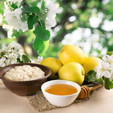 Yellow apples on the plate, honey in the bowl, oatmeal, twig of apple tree and knitted napkin on the wooden board in the garden