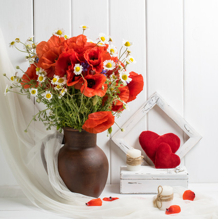 Red poppies in clay jug and two hearts on wooden planks background in rustic interior. Provence style.