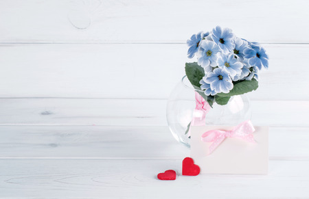 Bouquet of primroses in round vase with paper greeting card and two hearts Stock Photo