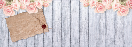 Roses and old paper with sealing wax on background of shabby wooden planks in rustic style