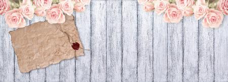 Rozen en oud papier met zegellak op de achtergrond van armoedige houten planken in rustieke stijl