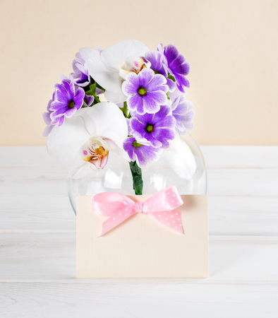 Bouquet of violet primroses and paper greeting card with bow on background of wooden planks in Shabby Chic style
