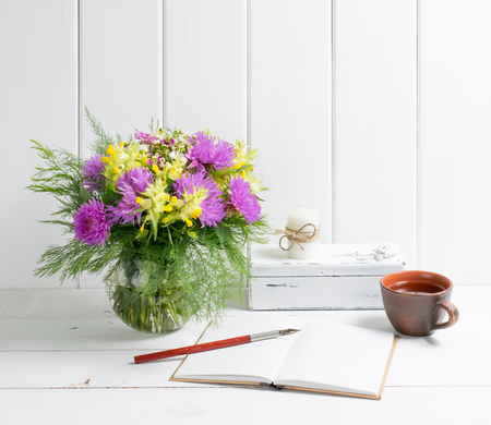 Flowers bouquet in glass round vase with open diary and cup tea, candle on casket, fountain pen on background of white wooden planks in provence style. Home interior. Stock Photo