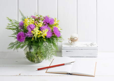 Flowers bouquet in glass round vase with open diary and candle on casket, fountain pen on background of white wooden planks in provence style. Home interior.