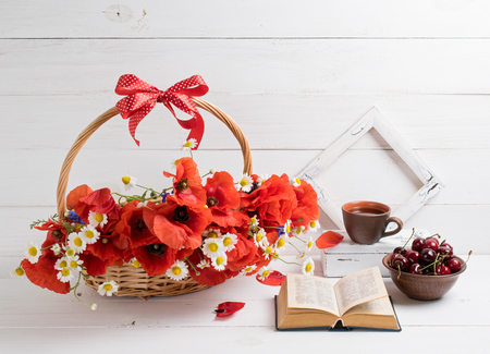 Daisy and poppies bouquet in basket with open book and cup tea, sweet cherry, photo frame on background of white wooden planks in provence style. Home interior.