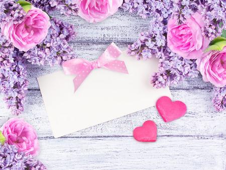 Fleurs de lilas et les roses carte de voeux de papier pour le texte et deux c?urs sur des planches de bois minable dans un style rustique. Vue de dessus. Banque d'images - 71245059