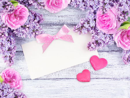 briar: Lilac flowers and roses with paper greeting card for text and two hearts on shabby wooden planks in rustic style. Top view.
