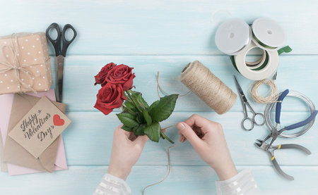 Valentine day theme. Top view of female hands wrap roses bouquet. Packed gifts, envelopes and tools on shabby wooden table. Workplace for preparing handmade decorations. Stock Photo