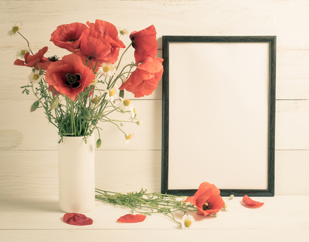 Red poppies bouquet in vase and motivational frame for text on background of white wooden planks in scandinavian style Stock Photo